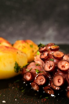 Köstliche gegrillte tintenfischtentakeln mit kartoffeln, gewürzt mit spanischem paprika, olivenöl, petersilie und meersalz