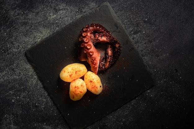 Köstliche gegrillte tintenfischtentakeln mit kartoffeln, gewürzt mit spanischem paprika, olivenöl und meersalz