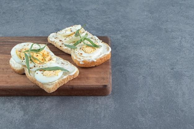 Köstliche gekochte eier mit toastbrot auf holzbrett.