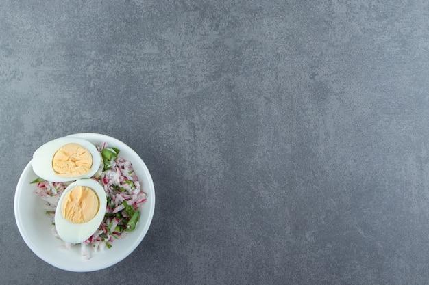 Köstliche gekochte eier und frischer salat in der weißen schüssel.