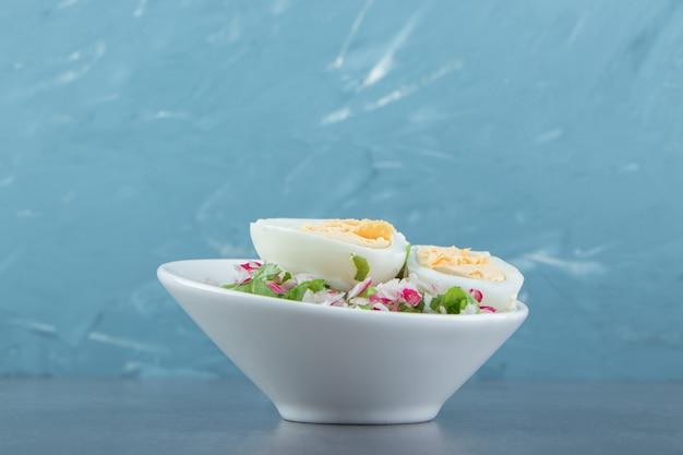 Köstliche gekochte eier und frischer salat in weißer schüssel