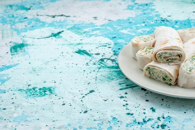 Köstliche gemüsebrötchen ganz und in scheiben geschnitten auf hellblauem schreibtisch, lebensmittelmehlrolle gemüsesnackfarbe