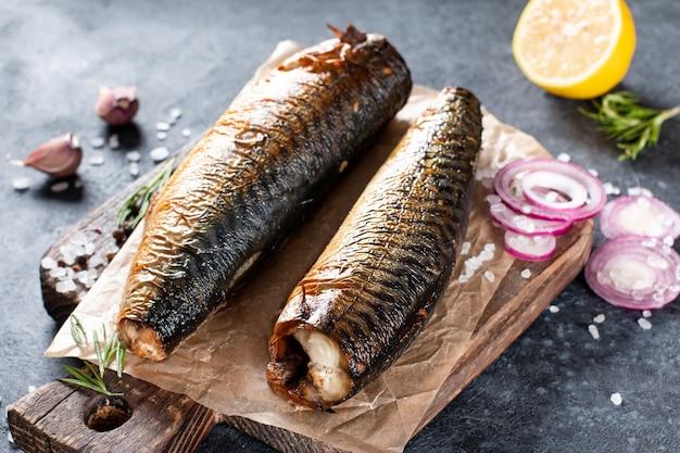 Köstliche geräucherte fischmakrele auf papier mit knoblauch- und zwiebelringen.