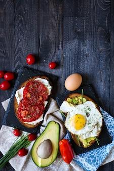 Köstliche geschmackvolle avocado-eier und tomaten-käse-toast