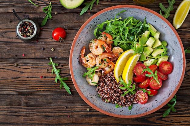 Köstliche gesunde buddha-schüssel mit garnelen, tomate, avocado, quinoa, zitrone und arugula auf dem holztisch. gesundes essen. ansicht von oben. flach liegen.