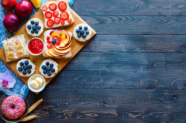 Köstliche gesunde frühstücksfruchtsandwiche mit unterschiedlicher füllungskäse-bananenerdbeerfischerbutterblaubeere auf einem anderen hölzernen hintergrund.