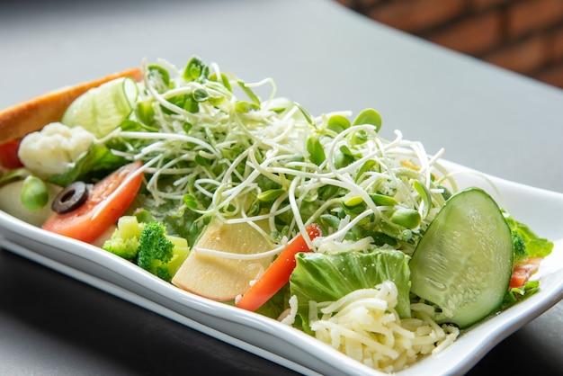 Köstliche gesunde gemüsesalatmischung von frischem auf weißer platte. essen hintergrund.