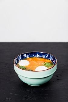 Köstliche gesunde gemüsesuppe mit fischball auf schwarzem schreibtisch