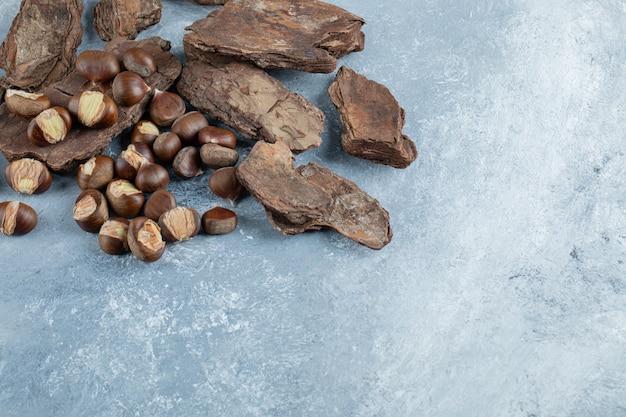 Köstliche gesunde kastanien auf einer baumrinde.