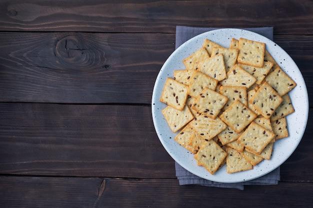 Köstliche gesunde kekscracker mit leinsamen und sesamsamen auf einem teller. hintergrund eines gesunden snacks, dunkler rustikaler holztisch. platz kopieren.
