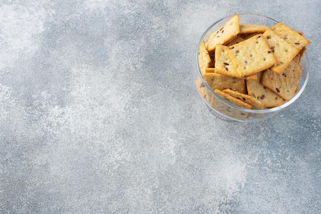 Köstliche gesunde kekscracker mit leinsamen und sesamsamen auf einem teller. hintergrund eines gesunden snacks, grauer betontisch, platz kopieren,
