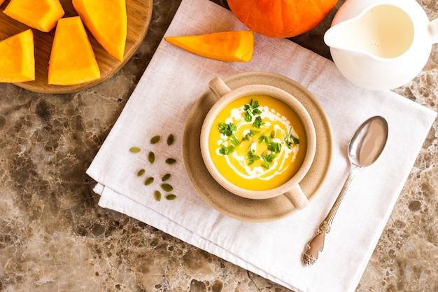 Köstliche gesunde kürbispüreesuppe mit sahne in einem suppenteller auf einem marmortisch. ansicht von oben.