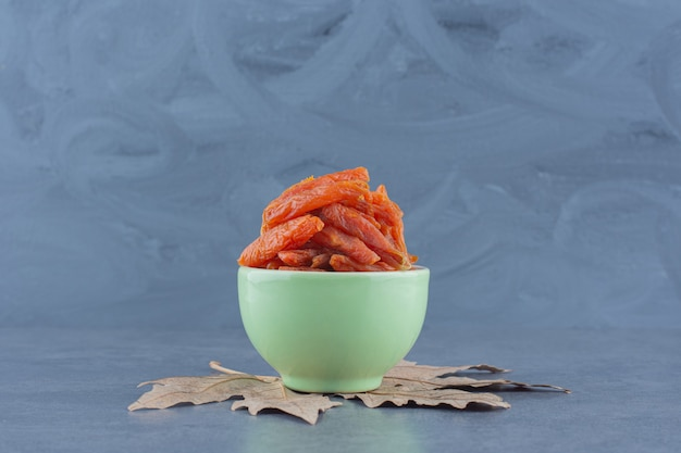 Köstliche getrocknete aprikose in der schüssel, auf dem blatt, auf dem marmorhintergrund.