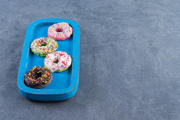 Köstliche glasierte donuts auf einem brett auf der marmoroberfläche