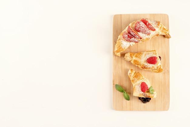 Köstliche goldene croissants gefüllt mit erdbeermarmelade. flache lage, draufsicht, kopierraum.