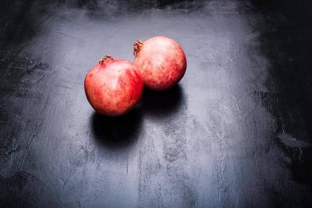 Köstliche granatapfelfrüchte auf schwarzem