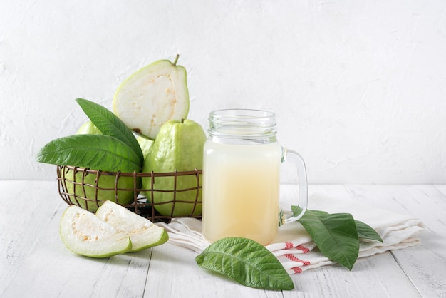 Köstliche guavenfrucht mit frischem saft auf hellweißem holztischhintergrund
