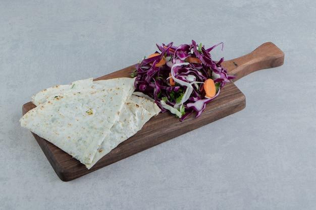 Köstliche gutabs mit salat auf dem brett, auf dem marmorhintergrund.