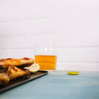 Köstliche hähnchenflügel auf tablett in der nähe von bier