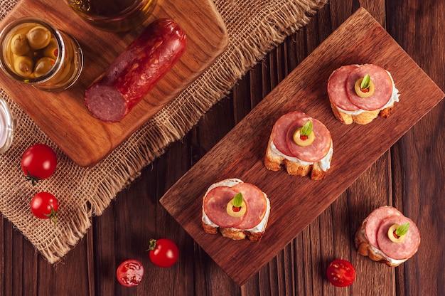 Köstliche häppchen mit salami, frischkäse, oliven und tomaten auf einem hölzernen hintergrund - draufsicht