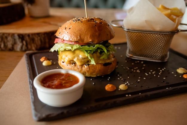 Köstliche hamburger mit pommes frites auf unscharfem hintergrund.