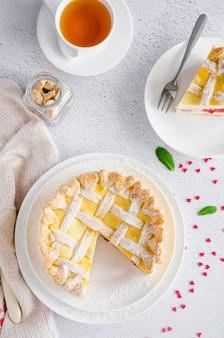 Köstliche hausgemachte blätterteigpastete mit frischkäsefüllung und kirsche auf einem weißen teller