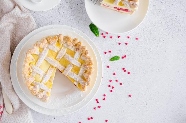 Köstliche hausgemachte blätterteigpastete oder kuchen mit frischkäsefüllung und kirsche auf einem weißen teller auf einem hellen steinhintergrund. dessert zum valentinstag. horizontale ausrichtung.