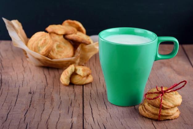 Köstliche hausgemachte duftende kekse, gebunden mit einem roten band, mit einer tasse frischer milch. feierlicher inhalt
