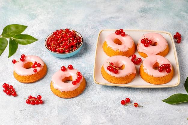 Köstliche hausgemachte glasur donuts mit roten johannisbeeren.