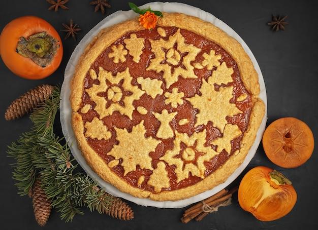 Köstliche hausgemachte kaki-marmeladen-torte. der kuchen ist mit weihnachtsfiguren aus keksen verziert.