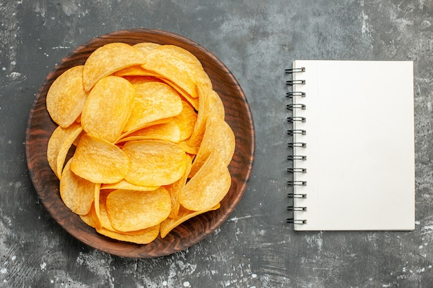 Köstliche hausgemachte kartoffelchips auf einem braunen teller und notizbuch auf grauem tisch