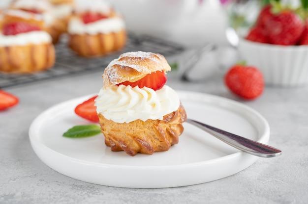 Köstliche hausgemachte kleine kuchen profiterole brandteig mit vanillepudding, erdbeere und puder auf grauem betonhintergrund. platz kopieren.