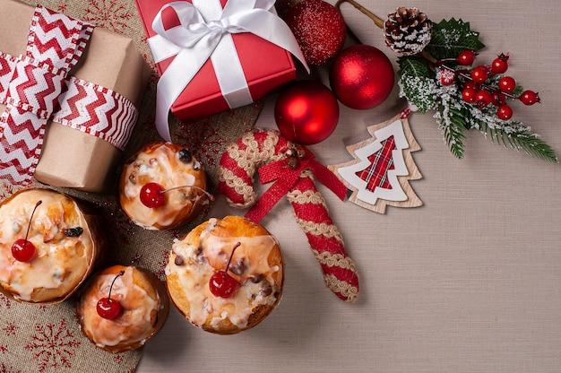 Köstliche hausgemachte mini-panettones zu weihnachten mit früchten und nüssen sowie weihnachtsschmuck