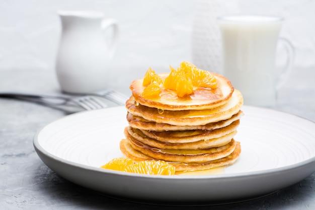 Köstliche hausgemachte pfannkuchen mit mandarinen und honig, glas milch auf einem teller auf dem tisch