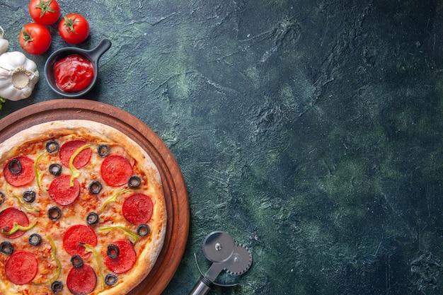 Köstliche hausgemachte pizza auf holzbretttomaten und essen auf dunkler, beunruhigter oberfläche
