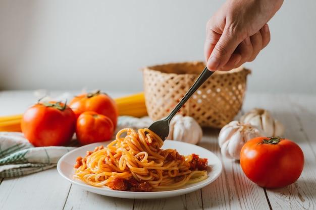 Köstliche hausgemachte spaghetti-nudeln mit tomatensauce und hackfleisch serviert auf einem weißen teller mit zutat auf weißem holzhintergrund. italienisches essen. hausgemachtes essen.