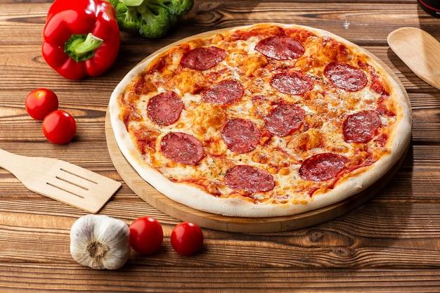 Köstliche heiße hausgemachte pepperoni-pizza auf dem holztisch. pepperoni pizza - frische hausgemachte pizza mit peperoni, käse und tomatensauce auf rustikalem schwarzem steinhintergrund mit kopienraum.