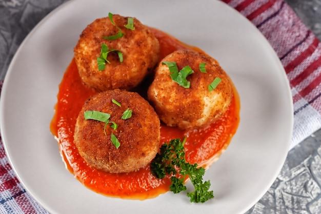 Köstliche heiße italienische arancini - reisbällchen gefüllt mit käse in tomatensauce, in einem teller auf einem alten holztisch