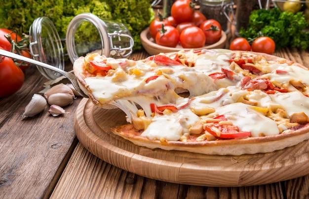 Köstliche heiße pizza auf hölzernem behälter mit schmelzendem käse