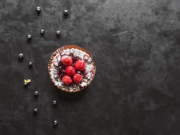 Köstliche herbe, bunte gebäckkuchen-süßigkeiten mit frischen himbeeren und blaubeeren auf schwarzem tisch.