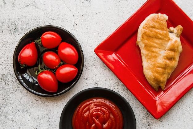 Köstliche hühnerflügel in der platte mit tomate und soße über konkretem hintergrund