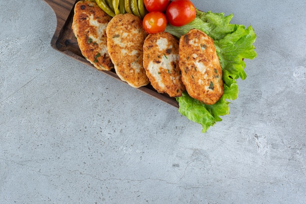 Köstliche hühnerschnitzel mit gemüse auf steintisch gelegt.