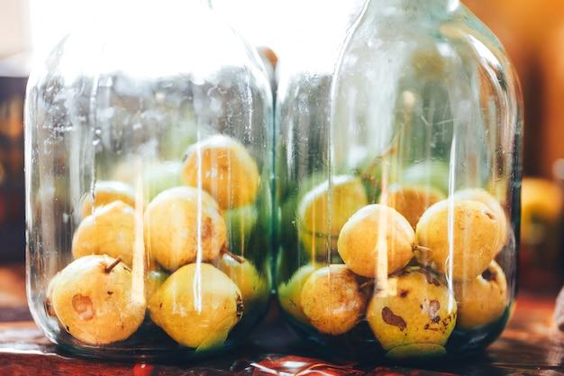 Köstliche in büchsen konservierte gelbe birnen in einem dunklen keller. kompott. hauptwintersnack im glasgefäß. glas mit birne isoliert auf. in büchsen konservierte birnen in der bank. nahansicht
