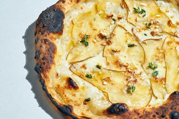 Köstliche italienische holzofenpizza mit cremiger sauce, cashewnüssen, birne, mozzarella und gorgonzola auf grauer oberfläche. hartes licht.