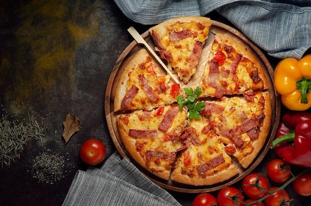 Köstliche italienische pizza schnitt schinken, speck und käse mit lebensmittelinhaltsstoffen auf alter küche