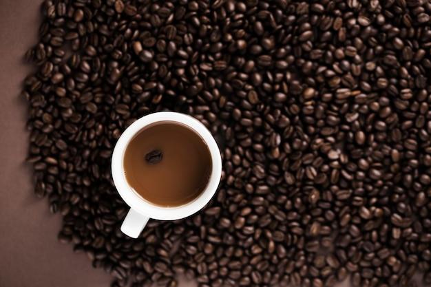 Köstliche kaffeetasse mit kaffeebohnehintergrund