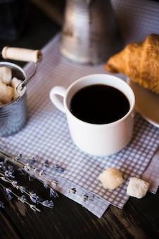 Köstliche kaffeetasse und hörnchen der hohen ansicht