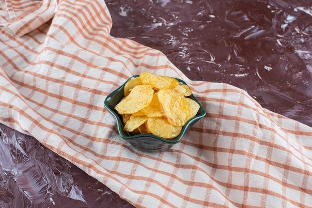 Köstliche kartoffelchips in einer schüssel auf geschirrtuch, auf dem marmortisch.