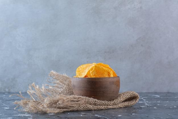 Köstliche kartoffelchips in holzschale auf textur, auf der marmoroberfläche