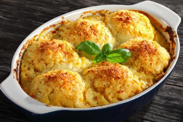 Köstliche kartoffelpolenta mit vegetarischen knödeln, gefüllt mit pilzen